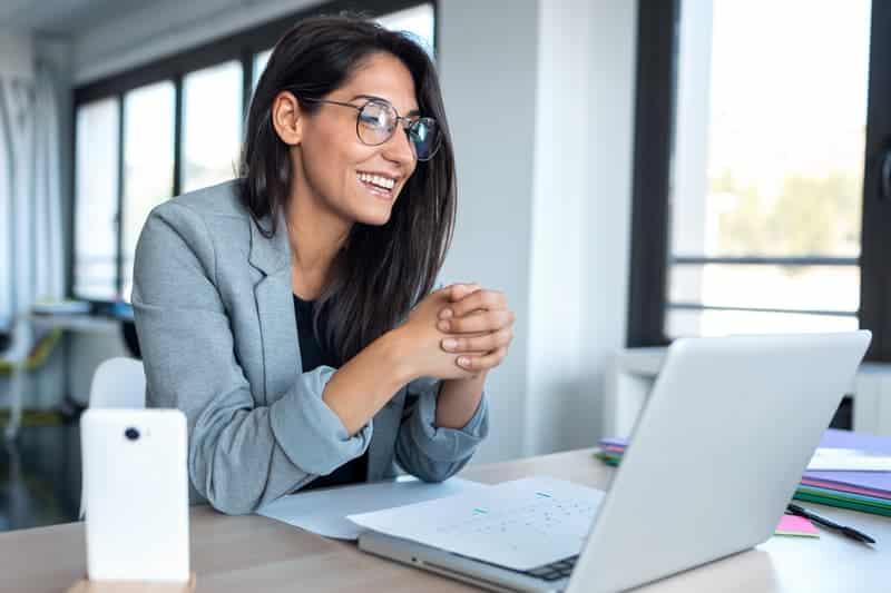 woman sitting at a desk enjoying new google meet updates