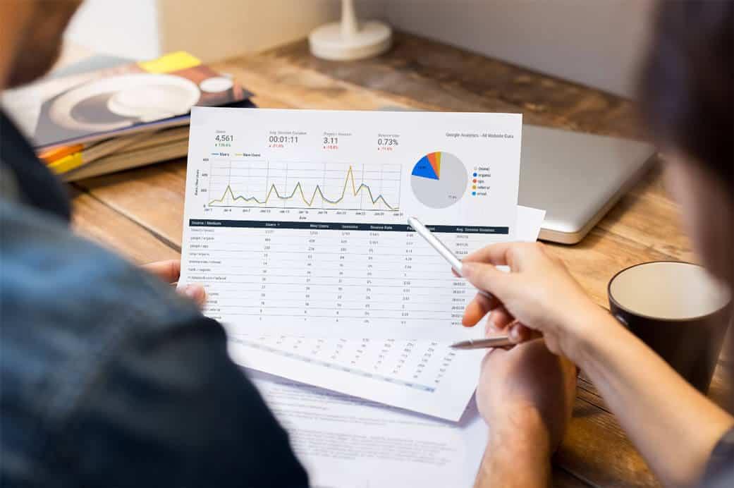 people looking at chart displaying google analytics