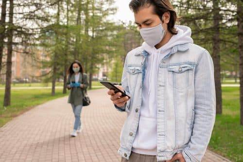 Man looking at ppc campaigns on his phone during a pandemic
